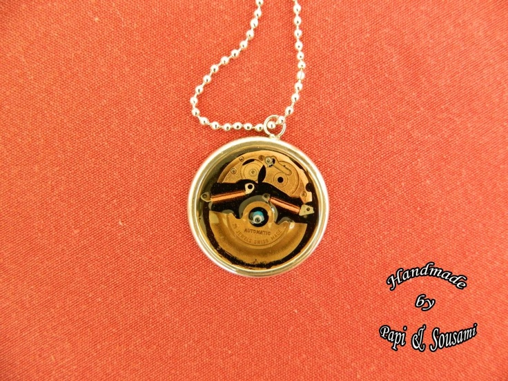 A steampunk resin pendant with tiny parts of old mechanical hand watch
