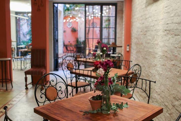 Mesas de convidados com decoração rústica romântica com suculentas, eucaliptos e flores nas cores vermelho, rosa e roxo.