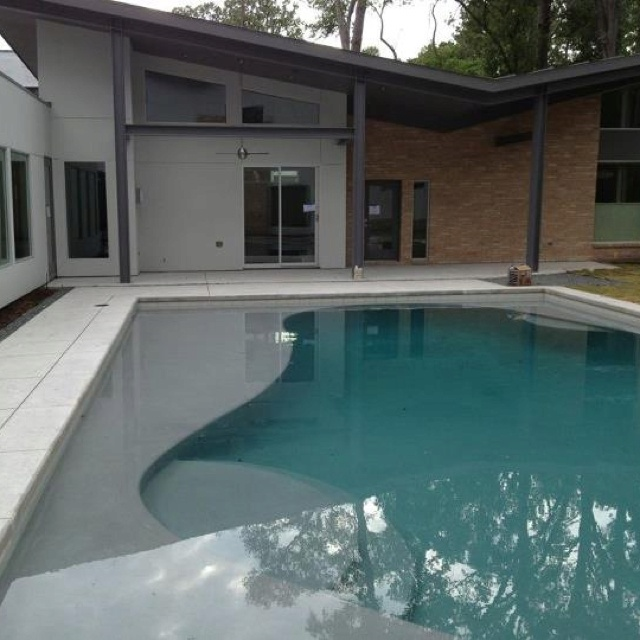 Old style kidney shape pool updated to reflect house renovation