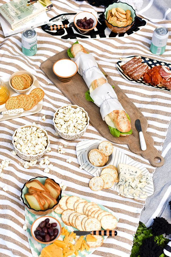 A picnic doesn't always have to be paper plates and finger sandwiches. Your specialty grocery store has great grab and go snacks that will provide a unique look to your outdoor spread. Don't forget colorful serveware!