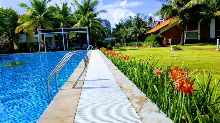 Color of life Pure morning with gentle sunshine, green garden, orange flowers, blue sky and swimming pool.  #Famianaresort #Phuquocisland