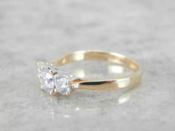 This classic vintage engagement ring is simple and traditional, crafted from 14 karat yellow gold. The three stones represent the past, present and the future. This will look well with a variety of wedding bands, from the ornate to the simple!  Metal: 14K Yellow and White Gold Center Diamond: .50 carats, 5.1mm, Round Cut, SI3 clarity, H color Side Diamonds: 2 diamonds weighing .46 carats Time Period: Vintage (1960's – 1990's) Size of Ring: 7½, but can be sized to fit almost any finger…