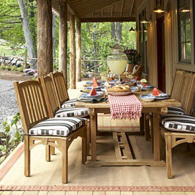 Outdoor furniture sets the scene for front porch dining. Transitional styling―simple lines and natural teak―make the dining set at home anywhere, including the primitive exterior of Whisper Creek Cottage.