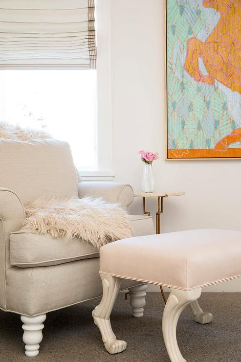 Sw snowbound A beige roll arm nursery chair seating in the corner of a cream and blush pink nursery is accented by a blush pink sheepskin throw blanket next to a pink hoof ottoman.