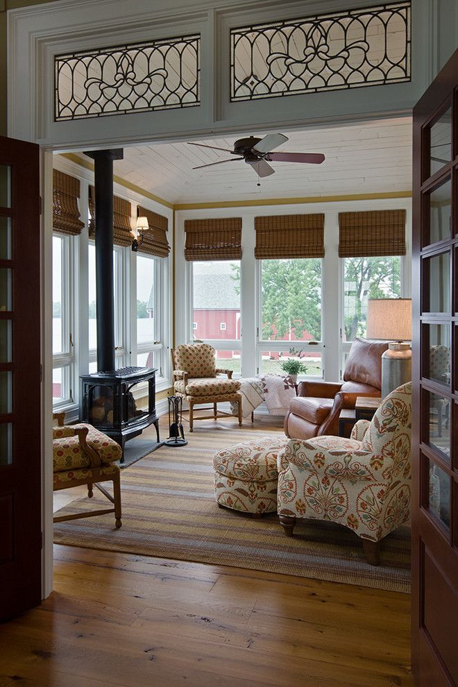 Sun room designs sunroom farmhouse with wood stove white framed windows traditional design table lamp floral upholstered armchair ceiling fan natural light brown leather recliner white tongue and groove ceiling roman shades sittin