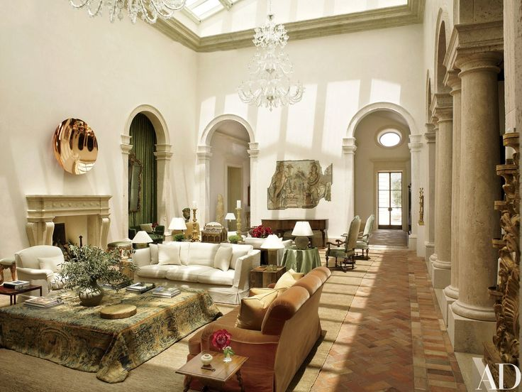 In the skylit living room, walls finished with integral plaster display a copper sculpture by Anish Kapoor and a Roman mosaic panel from the second century. Surrounding a massive cocktail table draped in an antique French tapestry are sofas and an armchair designed by Atelier AM; the ivory upholstery is a Loro Piana linen. The chandelier is Murano glass, and the hemp carpet is by Mansour.