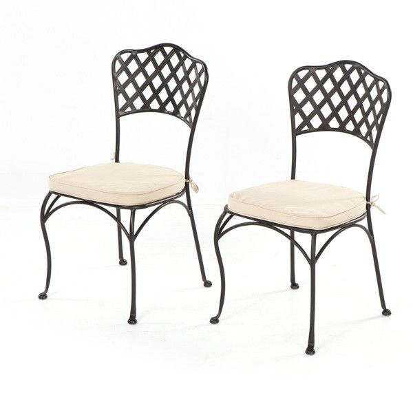 wrought Iron bistro chair is seen on the porch of a yellow home ...
