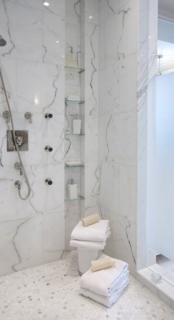 hex tile on shower floor (yours would be larger though), larger format tile on walls, and glass shelves in niche