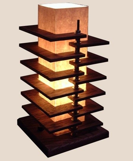 this handmade lamp features 12 oak panels that wrap around a 3.5x3.5 paper and fabric shade, cascading in alternating steps down to a 7x7 solid oak base. the panels are suspended by steel nuts on 2 threaded steel rods on either side of the shade.  the lamp is 13 high.