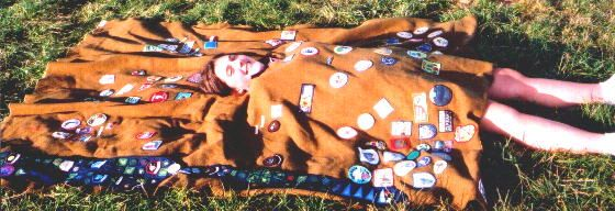 This blanket belongs to Emma Dean and the photo was taken at Kingsdown Scout Camp outside Dover, England in the summer of 2000.  Emma was a Girl Guide and to get the full blanket she agreed to lay down for the shot.  As you can see there is no rule about the color of the blanket or placement of badges.