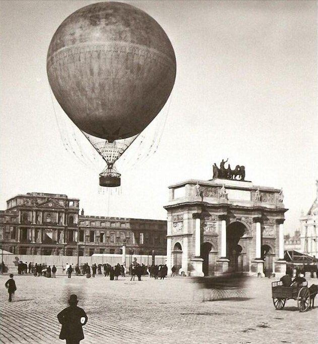 Une montgolfière s'envole de la place du Carrousel en 1878. Derrière l'Arc de Triomphe on voit le palais des Tuileries dont les ruines seront définitivement abattues en 1883  (Paris 1er)
