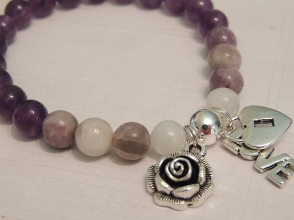 Bracelets by Anne Gale Jewels  **Stress / Anxiety Relief * Calming* Balancing * Healing **  Moonstone - Lepidolite - Amethyst   Rose Charm - Love & Heart Locket Charm  8mm gemstone beads with sterling silver metal bead and silver plated medals  Moonstone- A stone for new beginnings, Moonstone is a stone of inner growth and strength.  It soothes emotional instability and stress, and stabilises the emotions, providing calmness.  Moonstone enhances intuition, promotes inspiration, success and…