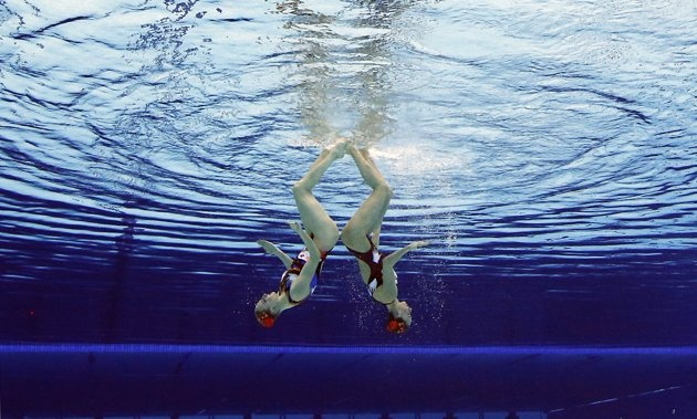 Natalia Ischenko and Svetlana Romanshina of Russia compete during women's duet synchronized swimming preliminary round at the Aquatics Centre in the Olympic Park during the 2012 Summer Olympics in London, Monday, Aug. 6, 2012.