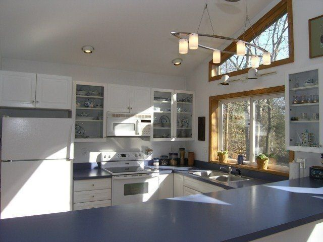 Cottage Kitchen with Wall sconce, U-shaped, Raised panel, Slate counters, Solid Surface Countertop in Midnight Pearl, Flush