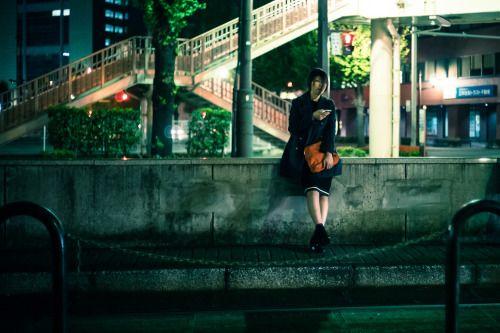 Een schoolmeisje zit op een muurtje op de trein te wachten.