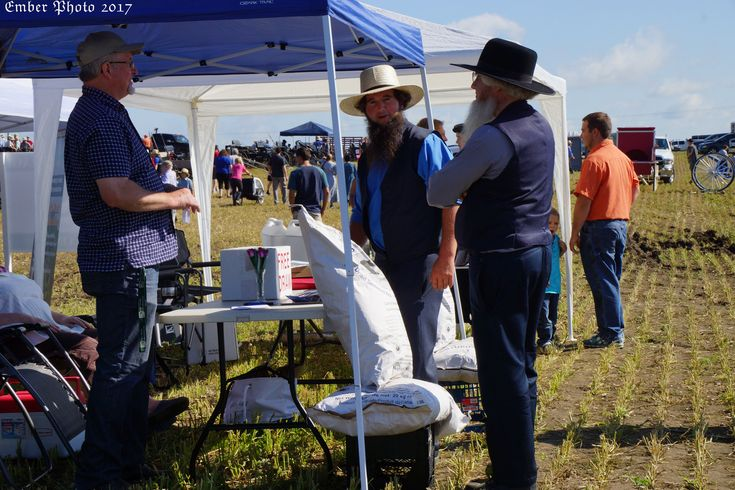 Two Amish men talk to a salesman at an auction event in Perth East, Ontario. The Amish man at the right in the black wool hat is visiting from the USA.