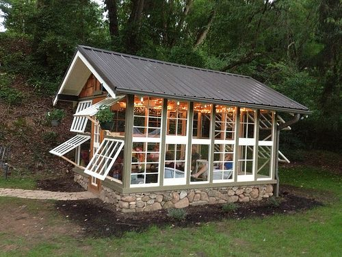 """The inspiration for the """"Summer House"""" started when Bill Kramer recovered 38 windows from an older house. He used old rock for the foundation (recovered from repairing the front steps on their 1930's rock cottage), recycled bricks for the floor, and leftover roofing. All of the lighting and the fan came from thrift stores. The wicker furniture and decor came from garage sales. A nice space to embellish their small house, Bill's """"summer house"""" wins the LIVE and/or WORK SPACE category."""