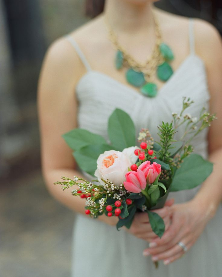 These bridesmaids held bouquets of roses and berries.