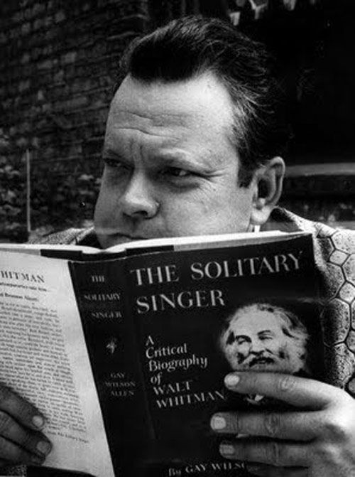 "Click through for 15 ""Photos of Celebrities Reading Books About Other Celebrities"" -- Shown: ""Orson Welles reading about Walt Whitman."""