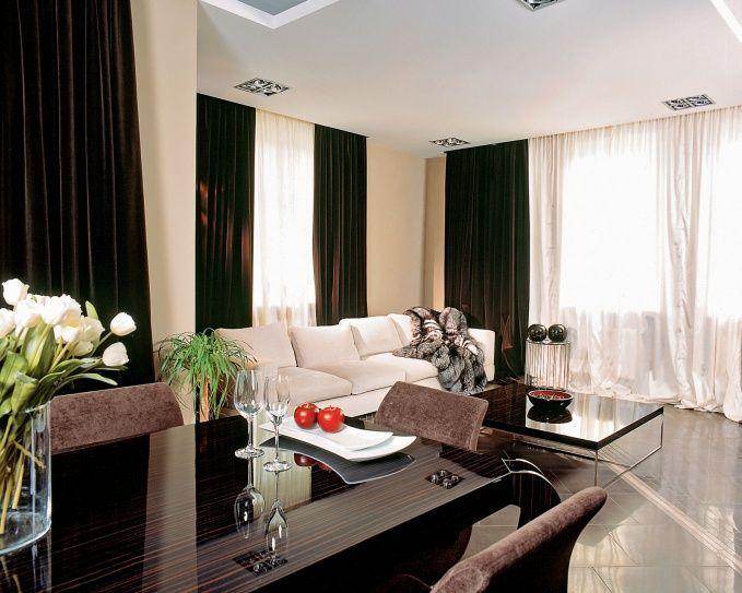 Темные шторы из плотного бархата создают интересный контраст с белыми занавесками.