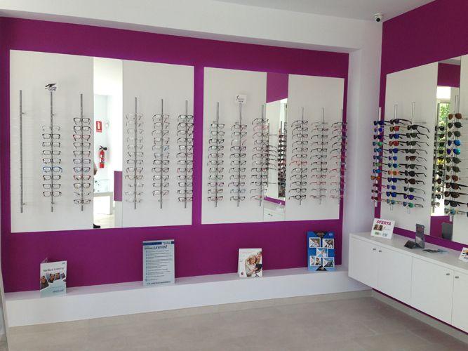 Reforma de óptica en Málaga - J.C. Ópticos.  El objetivo es unir el local al de farmacia, consiguiendo formas rectas, limpias y sencillas. Para ello se opta por tonos fríos como el morado, combinándolo con blanco roto en el mobiliario y en paredes. Y tonos grises muy neutros para los solados. Se busca una imagen de centro clínico, muy aséptico, todo a la vista donde el cliente se pueda mover con comodidad y probarse las gafas.  http://goo.gl/VLte1m