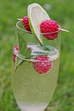 : Hugo. 1 GlasProsecco 1/2 Limette(n) 2 StängelMinze, frisch  Sirup (Holunderblüten-), nach Belieben  Eis, gewürfelt