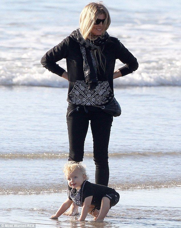 Adorable: The one-year-old was seen splashing about in the shallows while matching his mum...