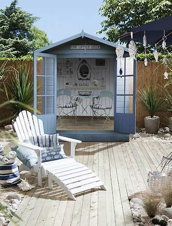 If you don't live near the seaside how about creating a coastal retreat in your garden. This is a cute beach style garden design idea, complete with shed (beach hut), hanging fish & more.