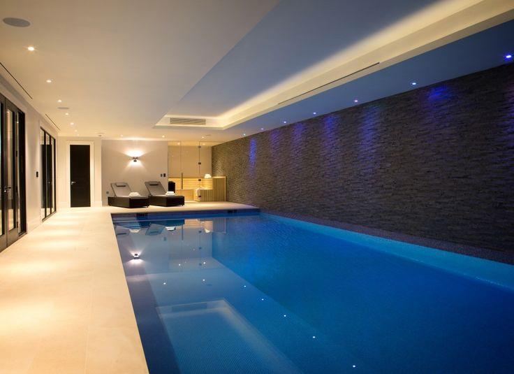 Colour changing ceiling downlights feature the textured tile back wall in this pool room.  LED ribbon in the coffered ceiling provides glare-free suabtle lighting.