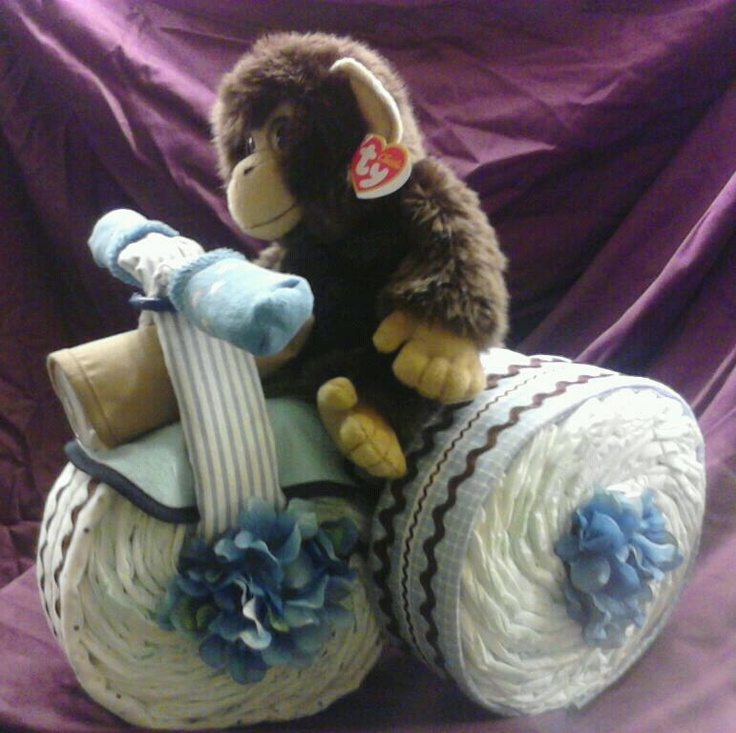 This is a Diaper Tricycle I made recently, it has 75 diapers, 5 blankets, one pair of socks, 2 bibs and a bottle, oh and one cute monkey!