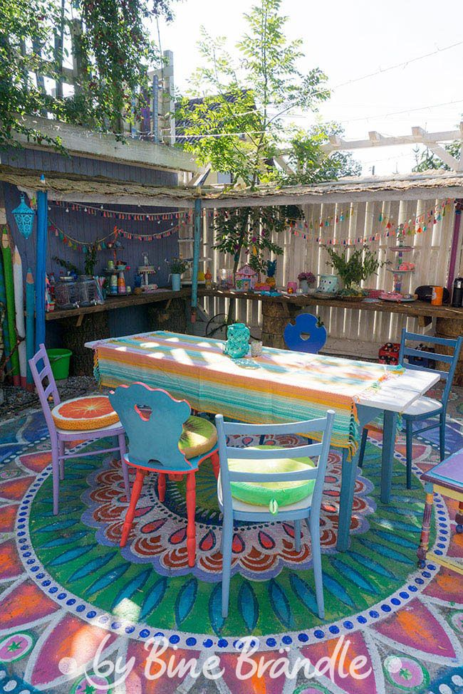 Colorful sitting area with giant mandala on concrete floor and a bar counter with Caribbean …