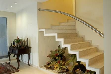 Projeto de jardim no espaço embaixo da escada dá charme à sala