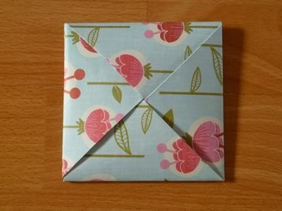 square origami envelope closed; opens into pinwheel shape, then the full square