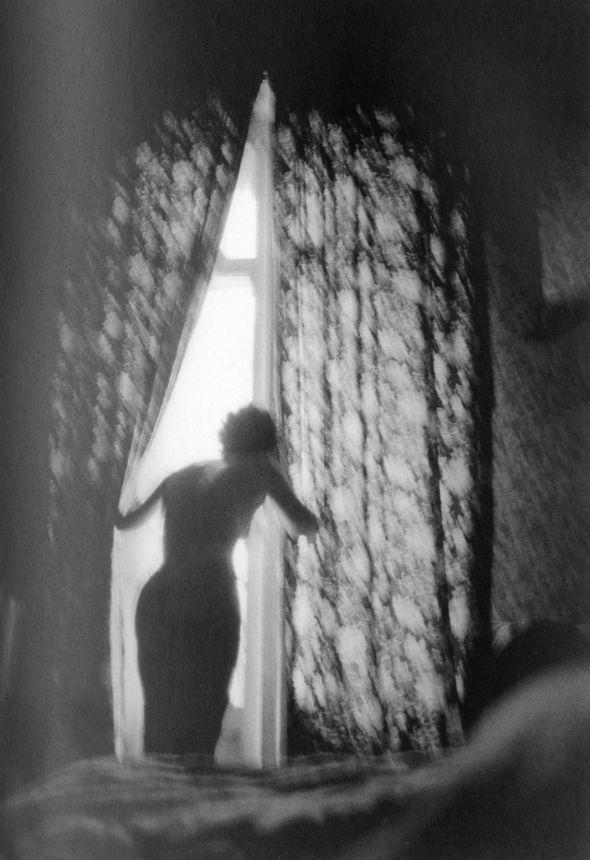 Erich Hartmann (1922-1999 American) • Pau. 1979. Woman looking out of Hotel Bedroom Window
