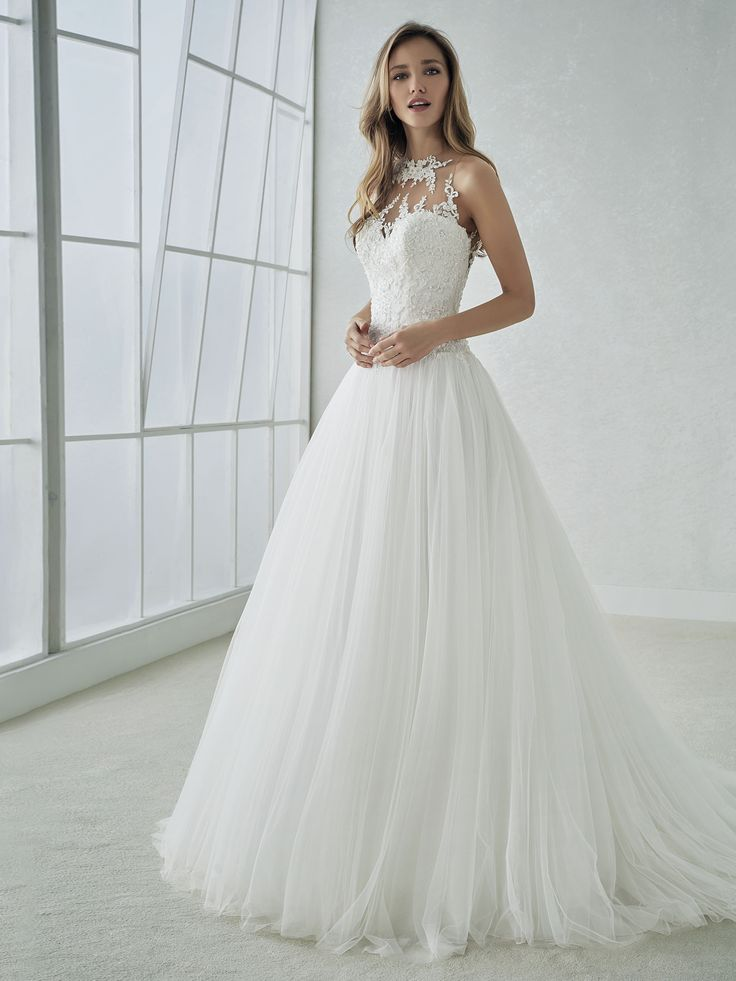 Sweet and very delicate. That describes the bride who wears this spectacular dress, with its tulle ballgown skirt that begins at the natural waistline and its sensual bodice featuring a halter illusion neckline and back. A marvelous wedding dress that plays with the illusions and the second-skin effect of the top part and the fullness and majesty of the bottom part.
