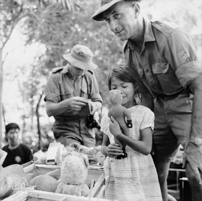 Warrant Officer Class 2 Sonny Phillips with a young Vietnamese girl during the distribution of clothing, toys and soap to peasant families in An Bac