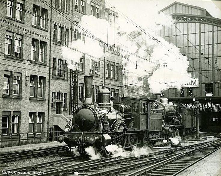 """Een goederentrein van Amsterdam Rietlanden naar Zaandam passeert het """"vijfde perron oost, IJ-zijde"""" van Amsterdam CS, getrokken door locs series 1000 (een zeer oud type) en 3700 in de jaren ′30."""