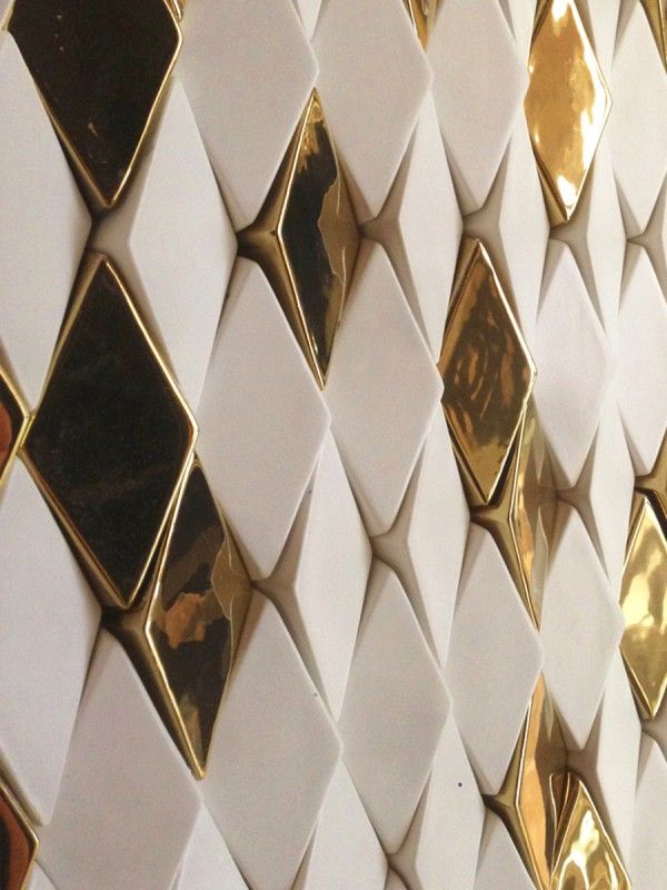 Gold tiles, the columns are composed of ceramic tiles in both matte white and high gloss gold finish, angled in varying directions to show reflect shimmer.