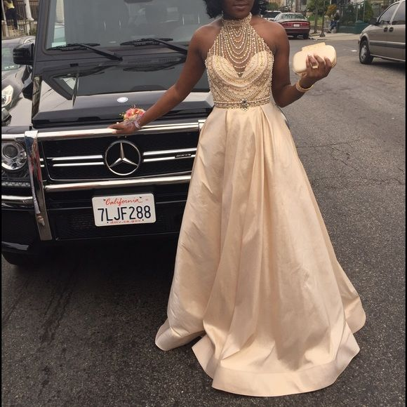 Champagne colored prom dress with pockets Long full length ball gown in a champagne color , two small makeup dots on the dress but hidden in pleats . It has a mid cut back and silver , gold and rose gold beaded bodice . Dresses Prom