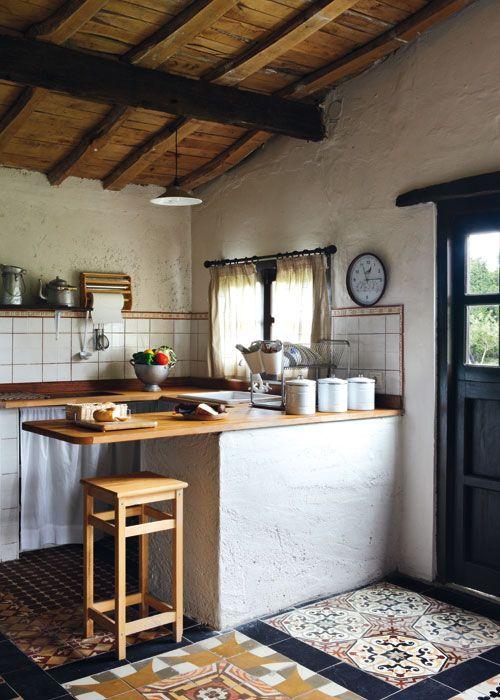 Toda la atención de esta cocina tan pequeña se la lleva el suelo, revestido en damero con hidráulicos de diferentes diseños.