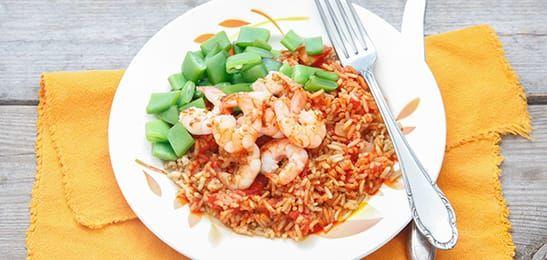 Gegrilde garnalen smaken goed bij de rijst met knoflook, tomaat en chilipoeder voor een beetje pit.
