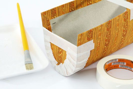 Com o pincel, passe bastante cola nas laterais do papel holler encapado, começando pela marcação de 3 cm a partir do topo. De dentro para fo...