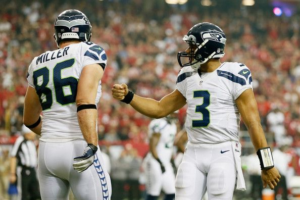 Zach Miller #86 and  Russell Wilson #3 of the Seattle Seahawks celebrate a fourth quarter touchdown against the Atlanta Falcons during the NFC Divisional Playoff Game at Georgia Dome on January 13, 2013 in Atlanta, Georgia.