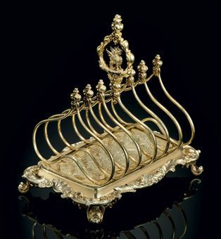 A WILLIAM IV SILVER-GILT TOAST RACK MARK OF PAUL STORR, LONDON, 1832 Rectangular on four leaf-clad feet, the base with shaped border and flat chased rocaille decoration, fishscale and diaper section, the double-arched frame with seven dividers and heraldic crest finial, the border engraved with a crest and coronet