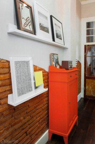 No corredor, sobre prateleiras apoiam-se quadros com fotos e ilustrações de artistas catarinenses que compõem com a cômoda laranja também reformada. Parede com tijolo aparente. Projeto do Studio UM Interiores.