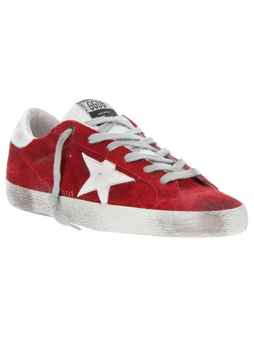 Red suede sneaker from Golden Goose featuring a round toe, a distressed white rubber sole, a white leather star logo at the outside panel, an embossed leather logo section at the back of the heel, and a front lace-up fastening.