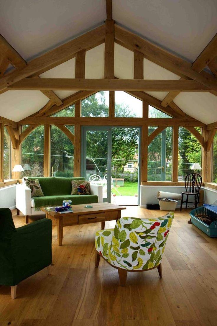 véranda en bois moderne aménagée avec plancher en bois, canapé blanc et fauteuil à motifs organiques