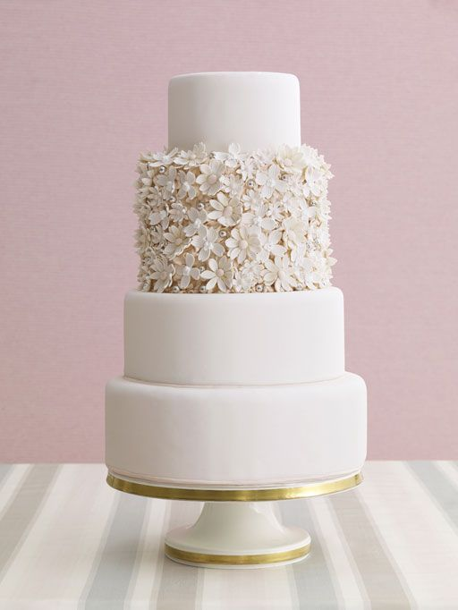 All-White: Cover the center tier of your cake with flowers to put a twist on the traditional all-white wedding cake.