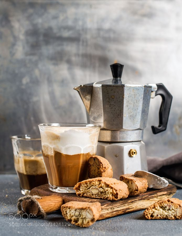 Pic: Glass of latte coffee on rustic wooden board cantucci biscuits and steel Italian Moka pot grey