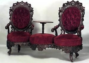American Victorian rosewood carved double swivel seat tete a tete with table center and red velvet upholstery